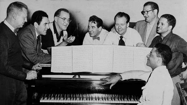 Benny Goodman (third from left) with some of his former musicians, seated around piano left to right: Vernon Brown, George Auld, Gene Krupa, Clint Neagley, Ziggy Elman, Israel Crosby and Teddy Wilson (at piano), 1952. World Telegram & Sun photo by Fred Palumbo. Library of Congress Prints and Photographs Division. Public domain.