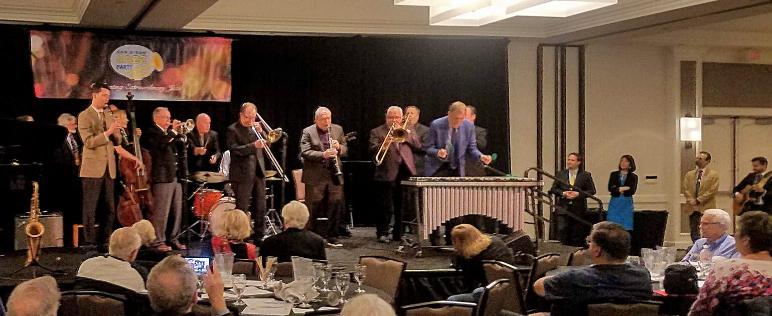 Finale with Richard Simon, Evan Arntzen (cl), Nicki Parrott (bs), Ed Polcer (cnt), Eddie Metz, Jr. (on cymbals), Danny Coots (dr, obscured), Bill Allred (tb), Ken Peplowski (cl), Dan Barrett (tb), Harry Allen (sx), Chuck Redd (vibes), Jon-Erik Kellso (tp, obscured) while Paolo Alderighi, Stephaie Trick, Rossano Sportiello and Vinny Raniolo wait to the side
